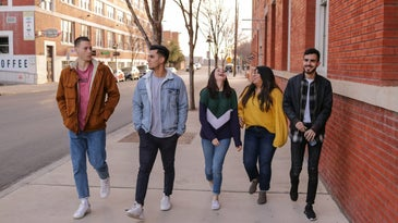A group of five teen walking down the street