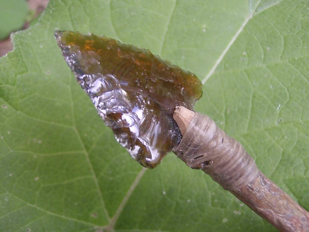A glass arrowed knipped from the shards of a broken beer bottle.