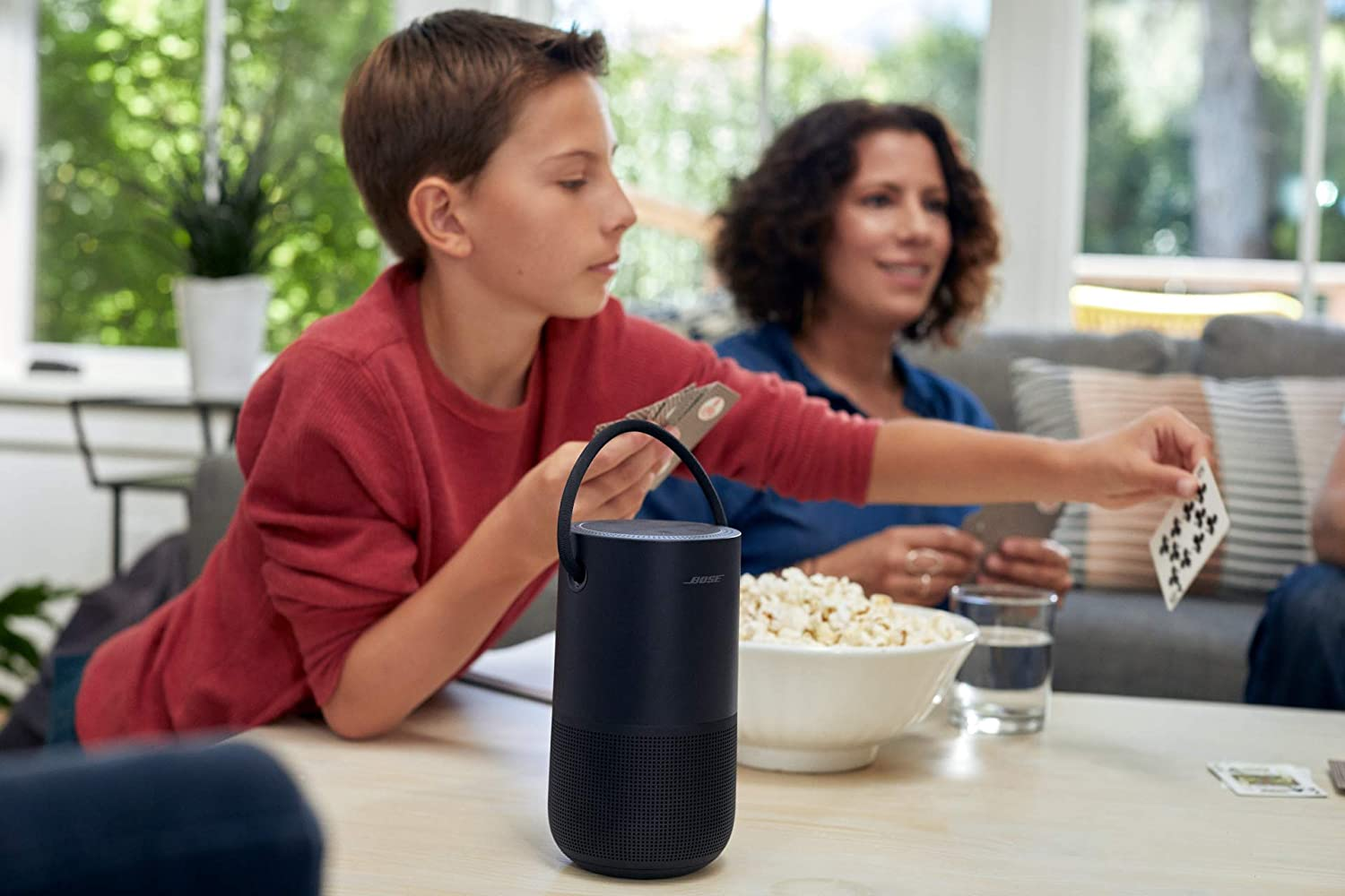 family sitting around table with speaker