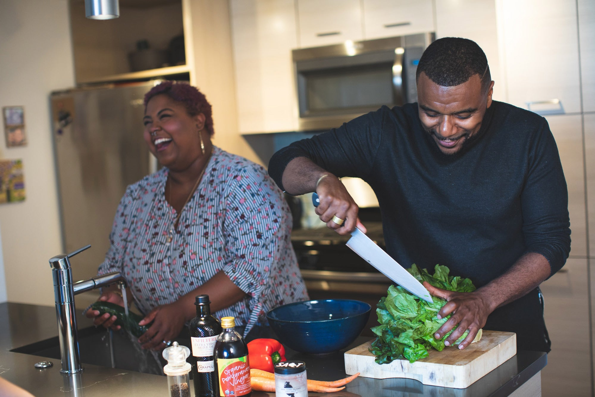 Black man and woman couple cooking with salad ingredients in kitchen