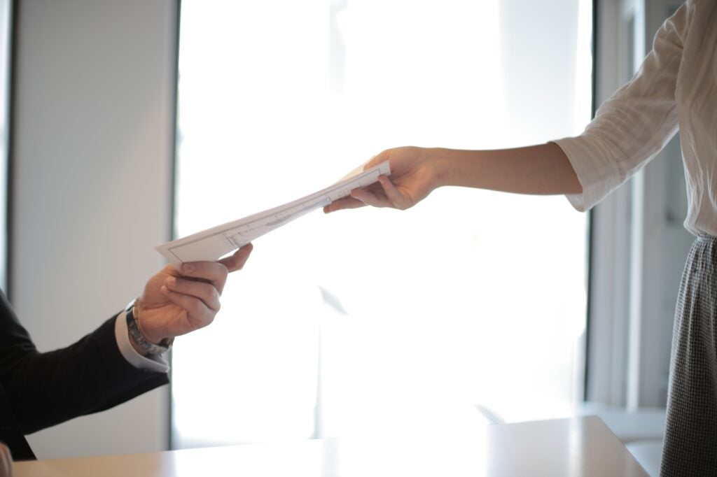 a person handing documents to another person in a business setting