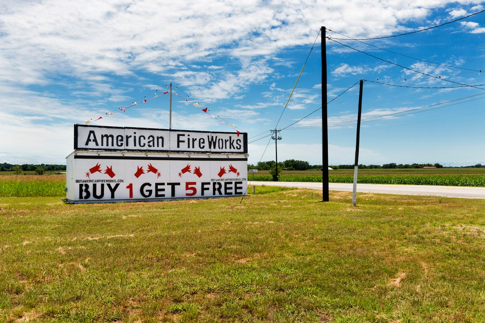 A sign for buy one, get five fireworks for free on a rural Texas highway