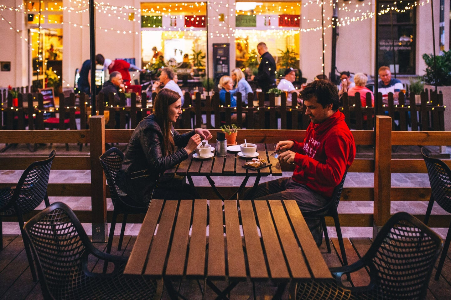 two people eating outside at a restaurant