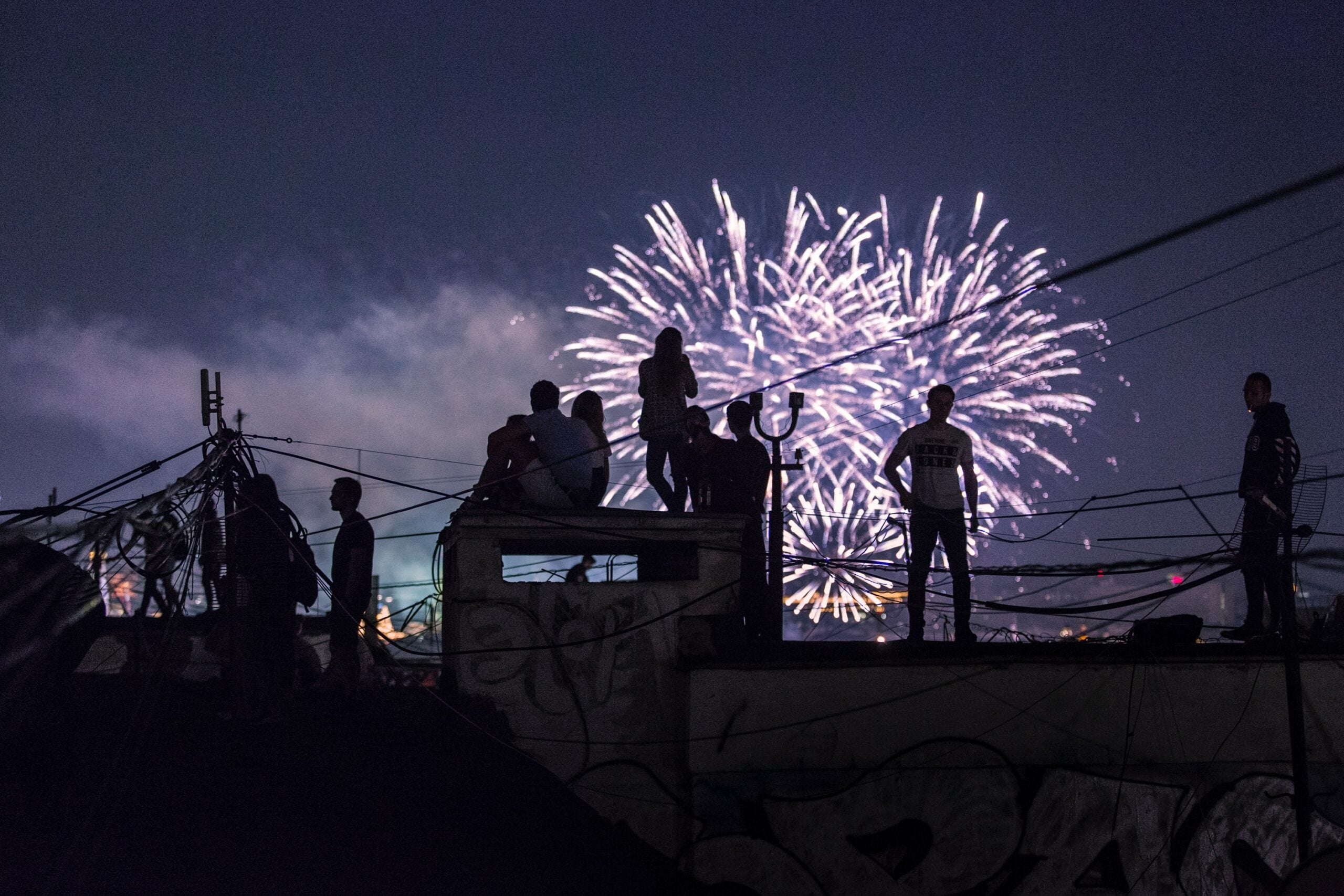 A group watching fireworks from a roof