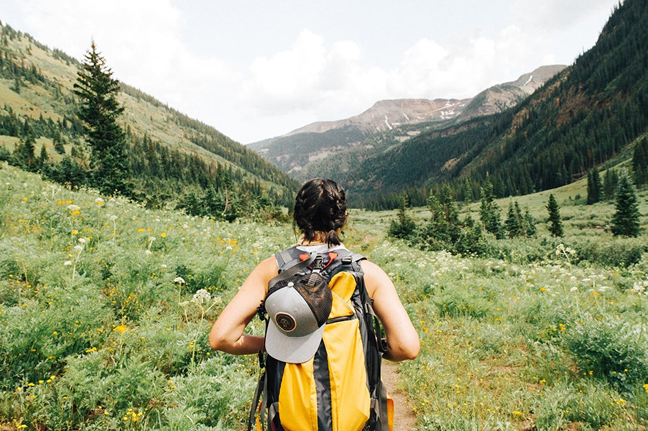 person walking with backpack through mountains