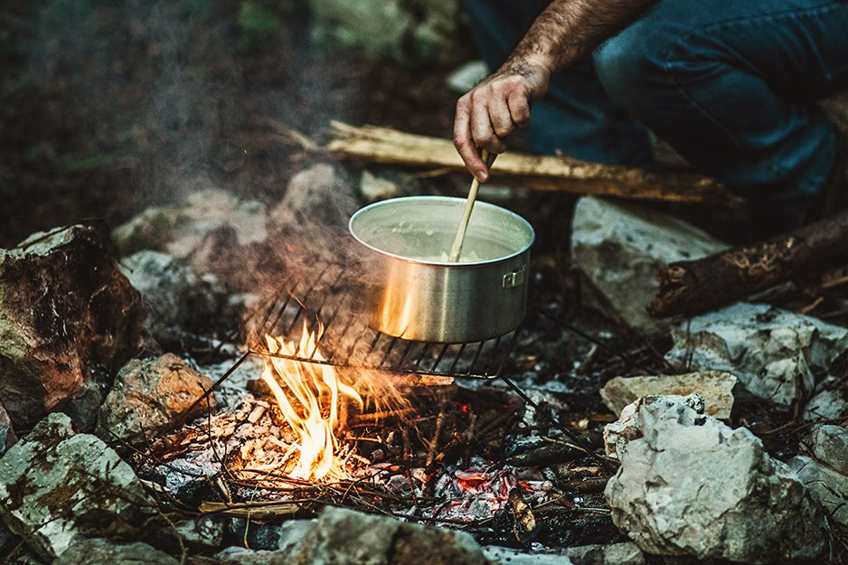 person cooking over campfire