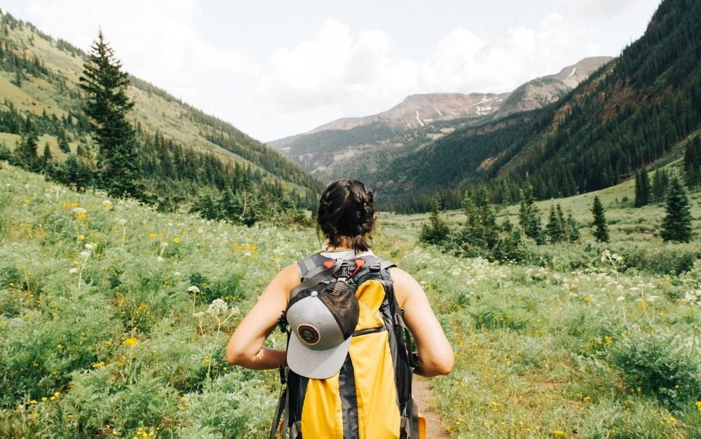A woman walking into the mountains with a hiking backpack with black and yellow color and a grey hat over it.