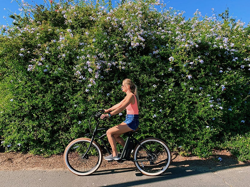 person riding an electric bike in front of a bush