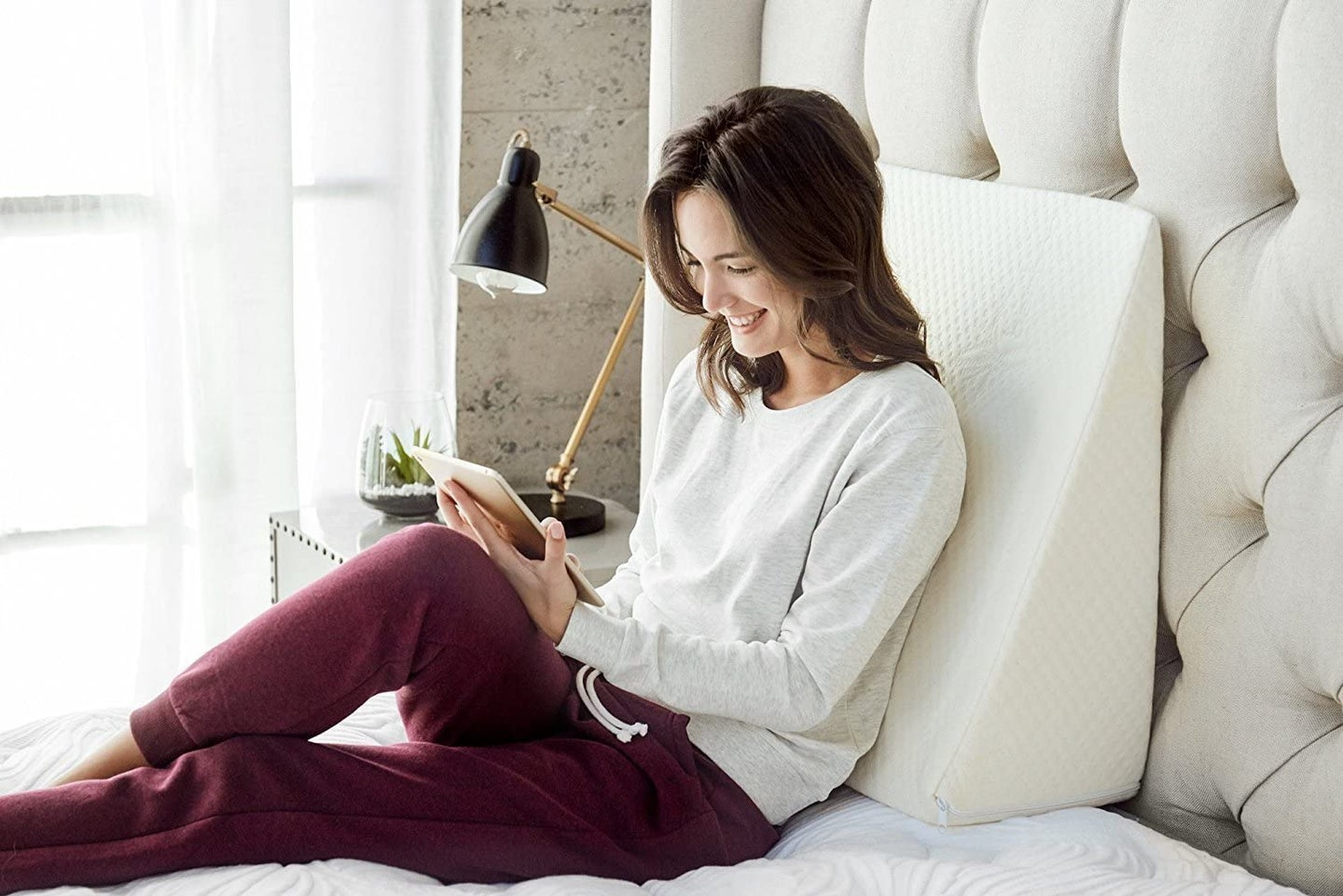person sitting on bed with wedge pillow