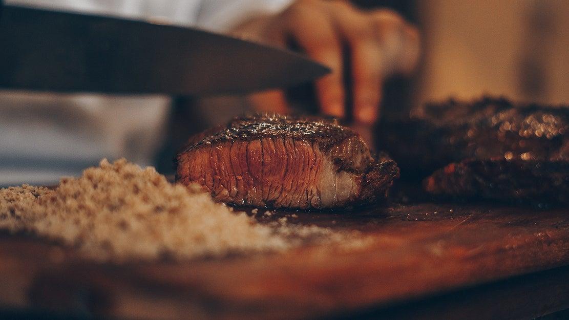 person cutting up a steak