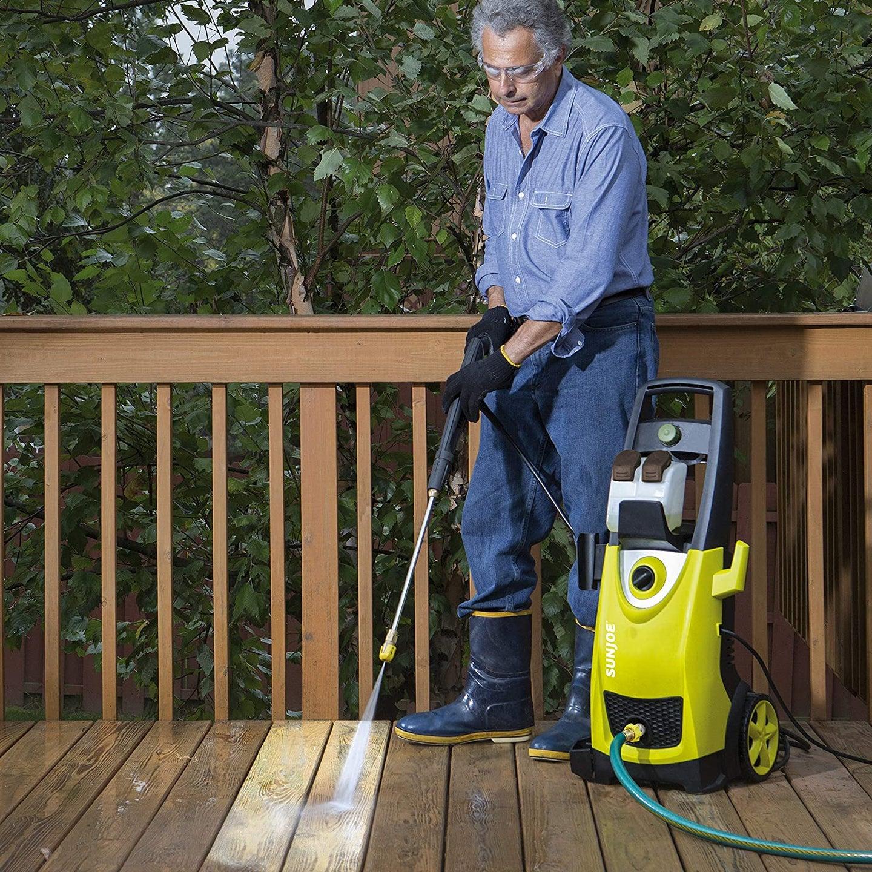 person pressure washing their deck