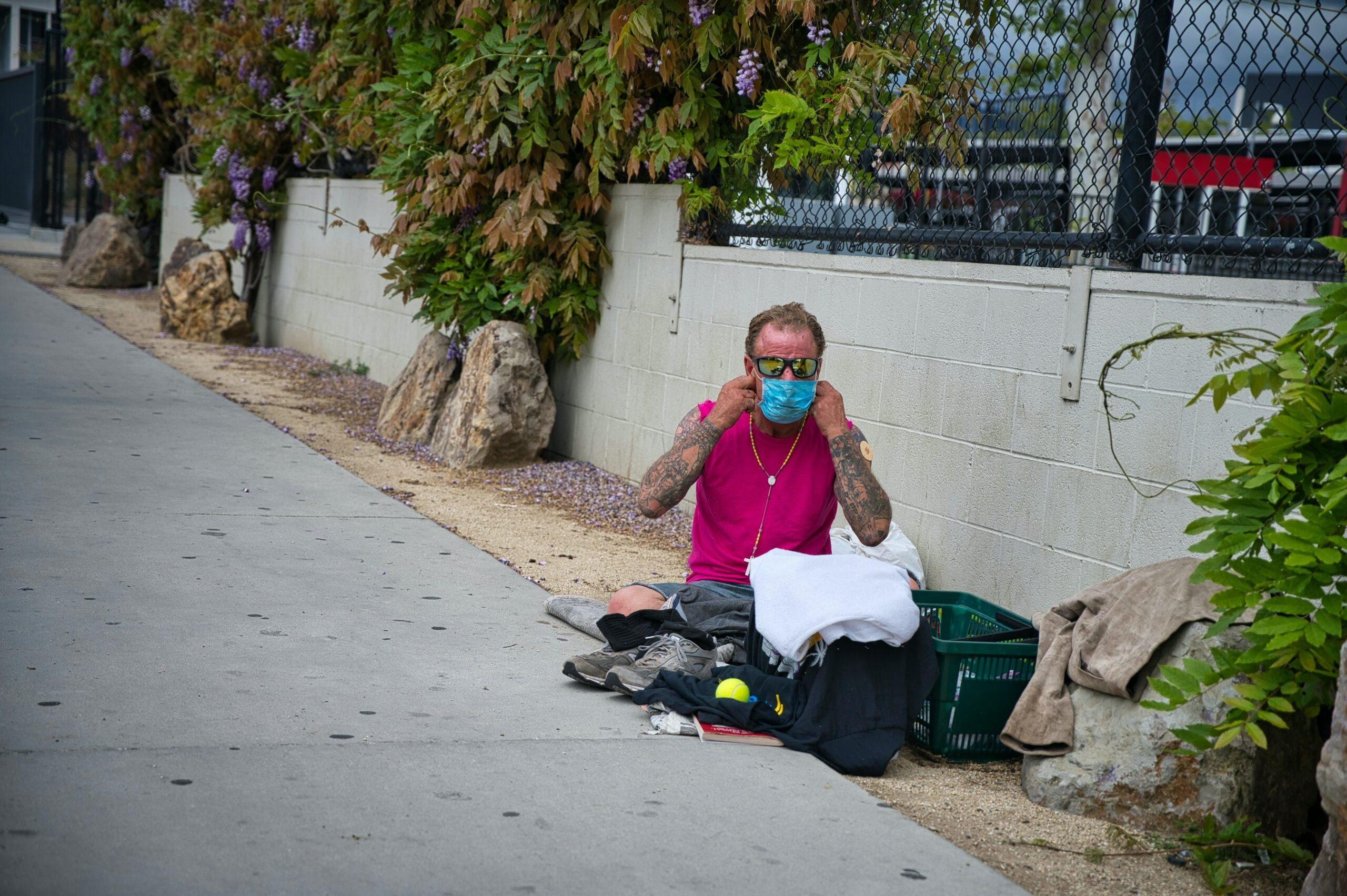 homeless man puts on face mask