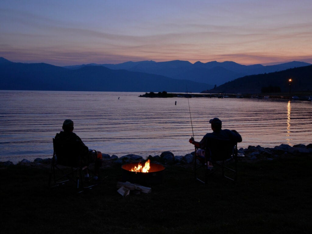 two people sitting by the water, burning a campfire and fishing at sunset