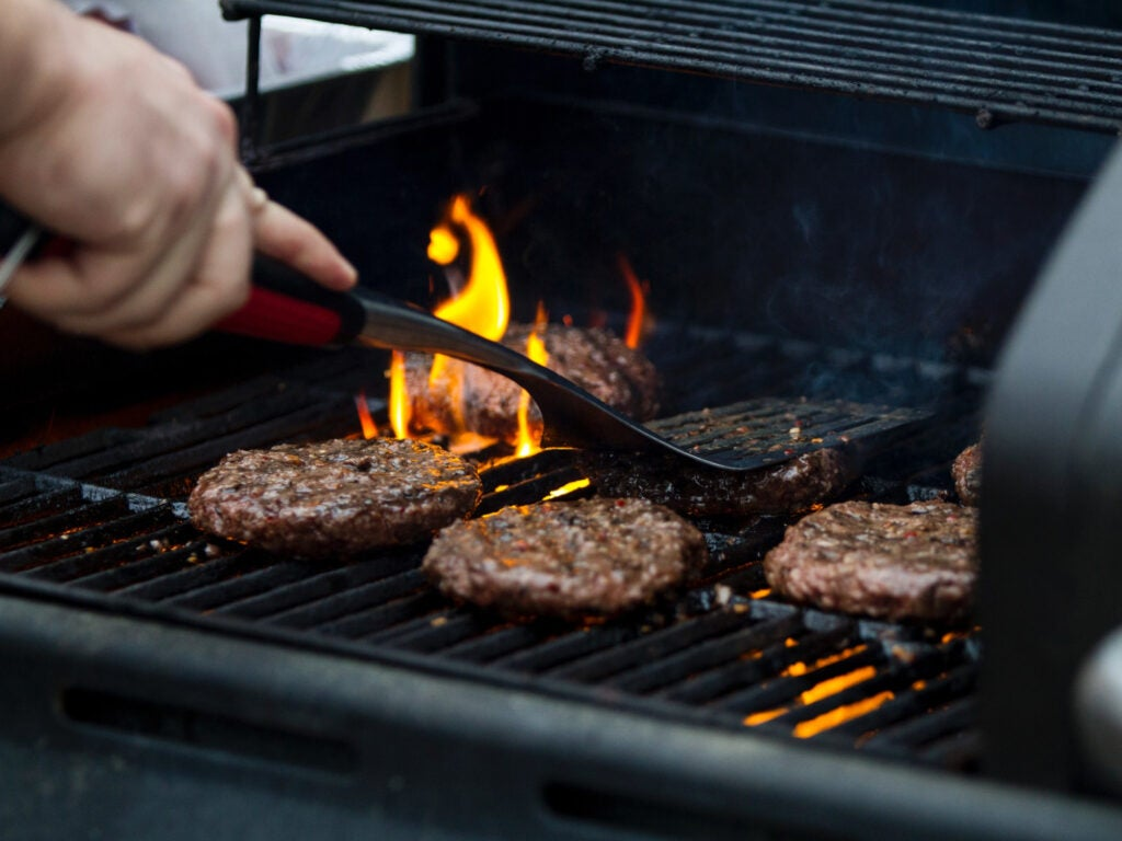 a person cooking burgers on a grill.