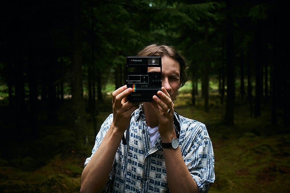 person holding instant camera