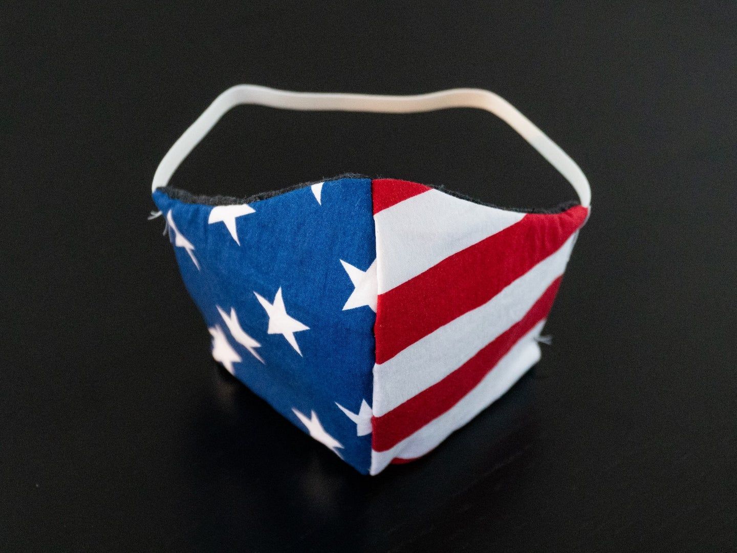 an American-flag patterned face mask on a black background.