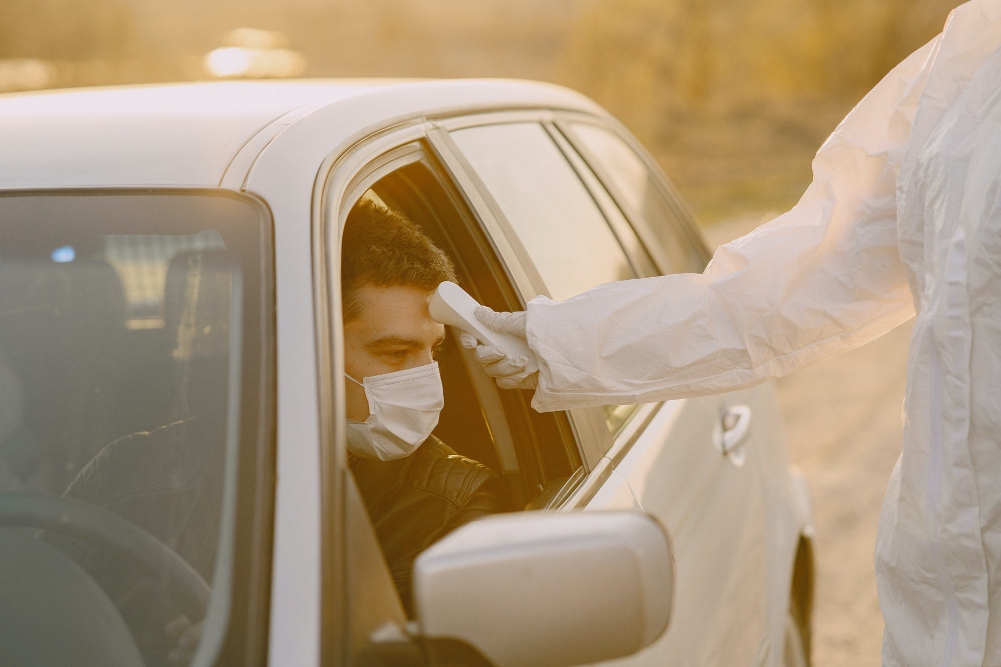 a man in a car wearing a mask is having his temperature taken by someone wearing protective gloves