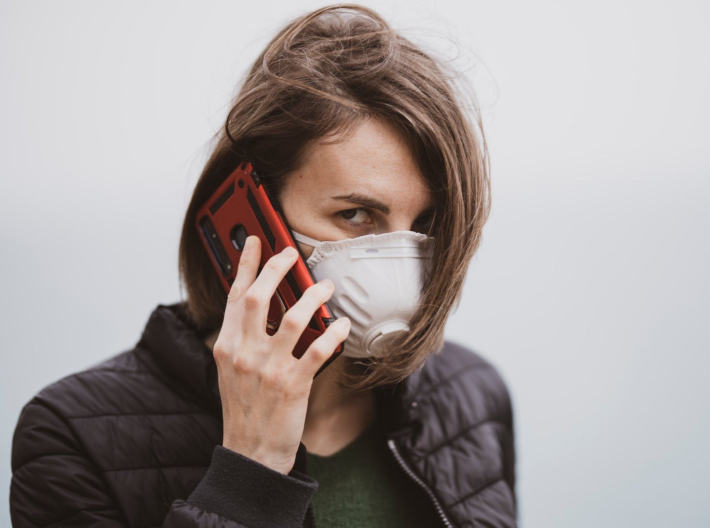a woman is talking on the phone while wearing a protective face mask. The mask is white and has a plastic valve on the front of it.