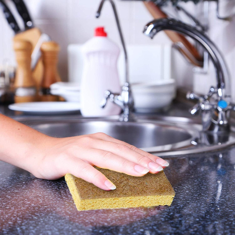 person scrubbing counter with sponge