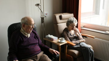 two older people sitting in chairs