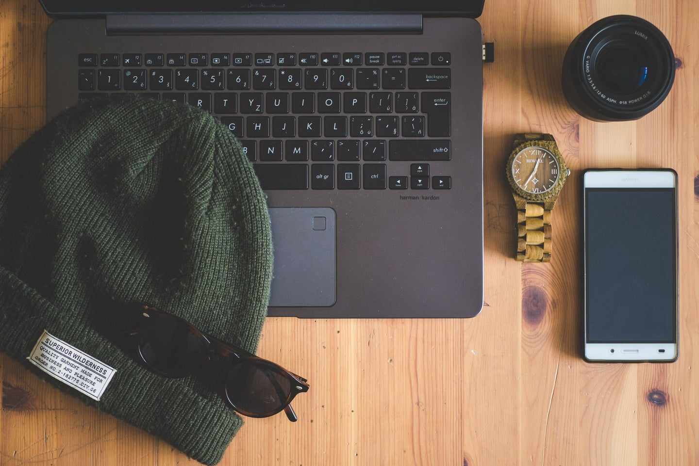 A laptop and iPhone with a beanie and sunglasses laid on top