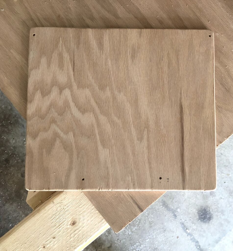 a piece of plywood cut, sanded, and drilled for the face of a DIY cutting board storage rack on the inside of a cabinet door