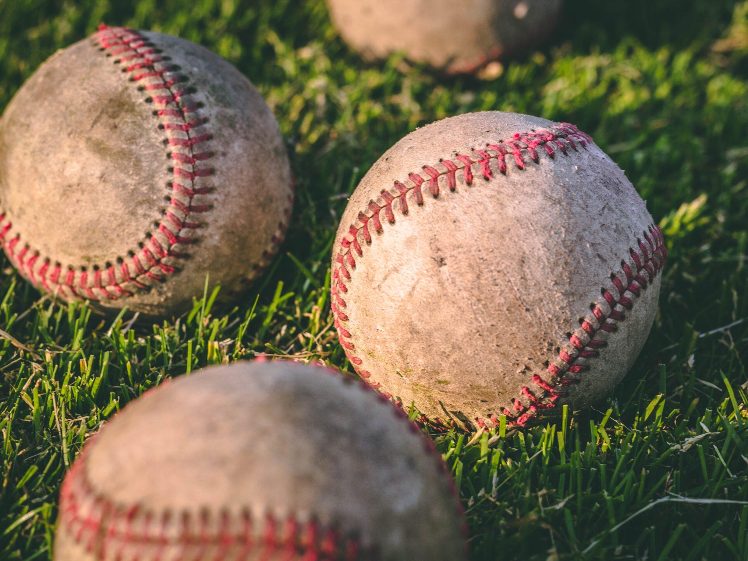 Baseballs sitting in a grassy field.