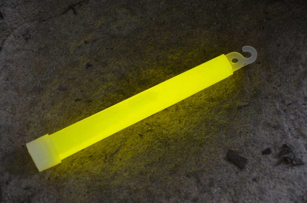 A yellow glowstick on the ground at night.