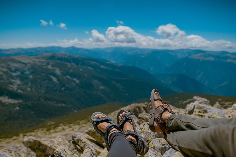 people hiking on a mountain in sandals