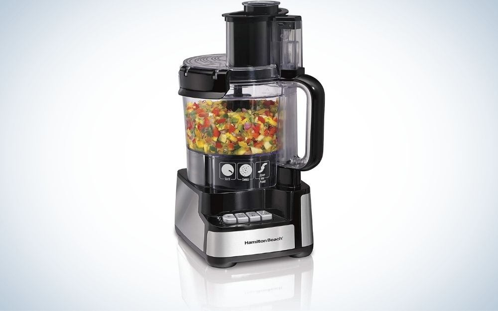 A gray and black vegetable grinder with chopped vegetables inside.