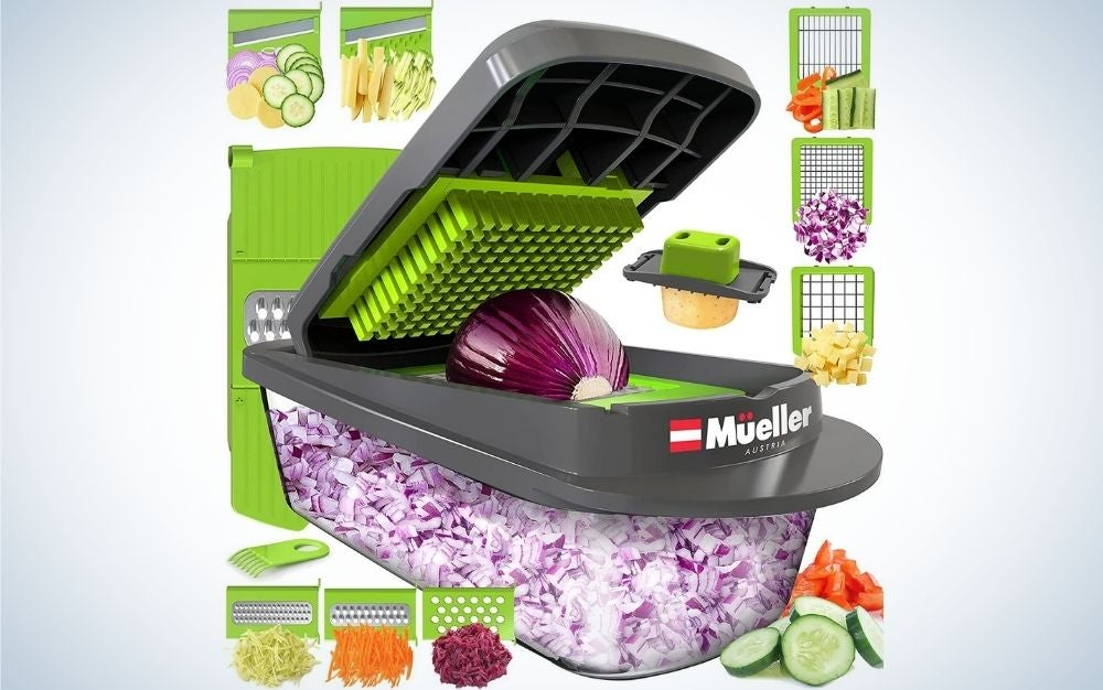 A dark grey vegetable shredder with a red onion inside it and with chopper filling and other demonstrative vegetables on its side.