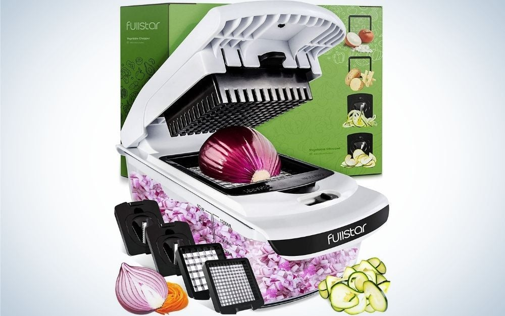 A white vegetable shredder with a red onion inside it and with chopper filling and other demonstrative vegetables on its side.