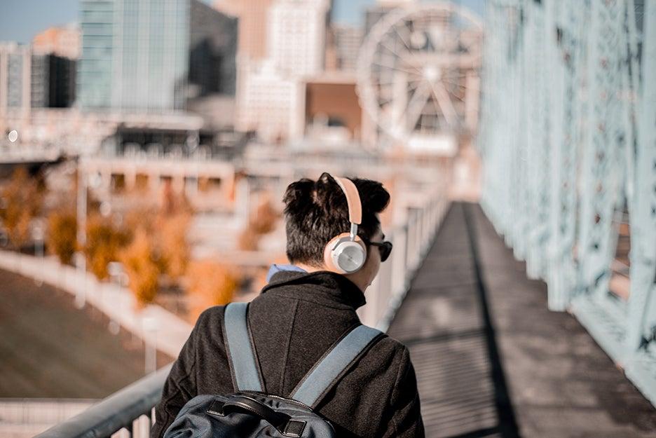 person walking over bridge with headphones