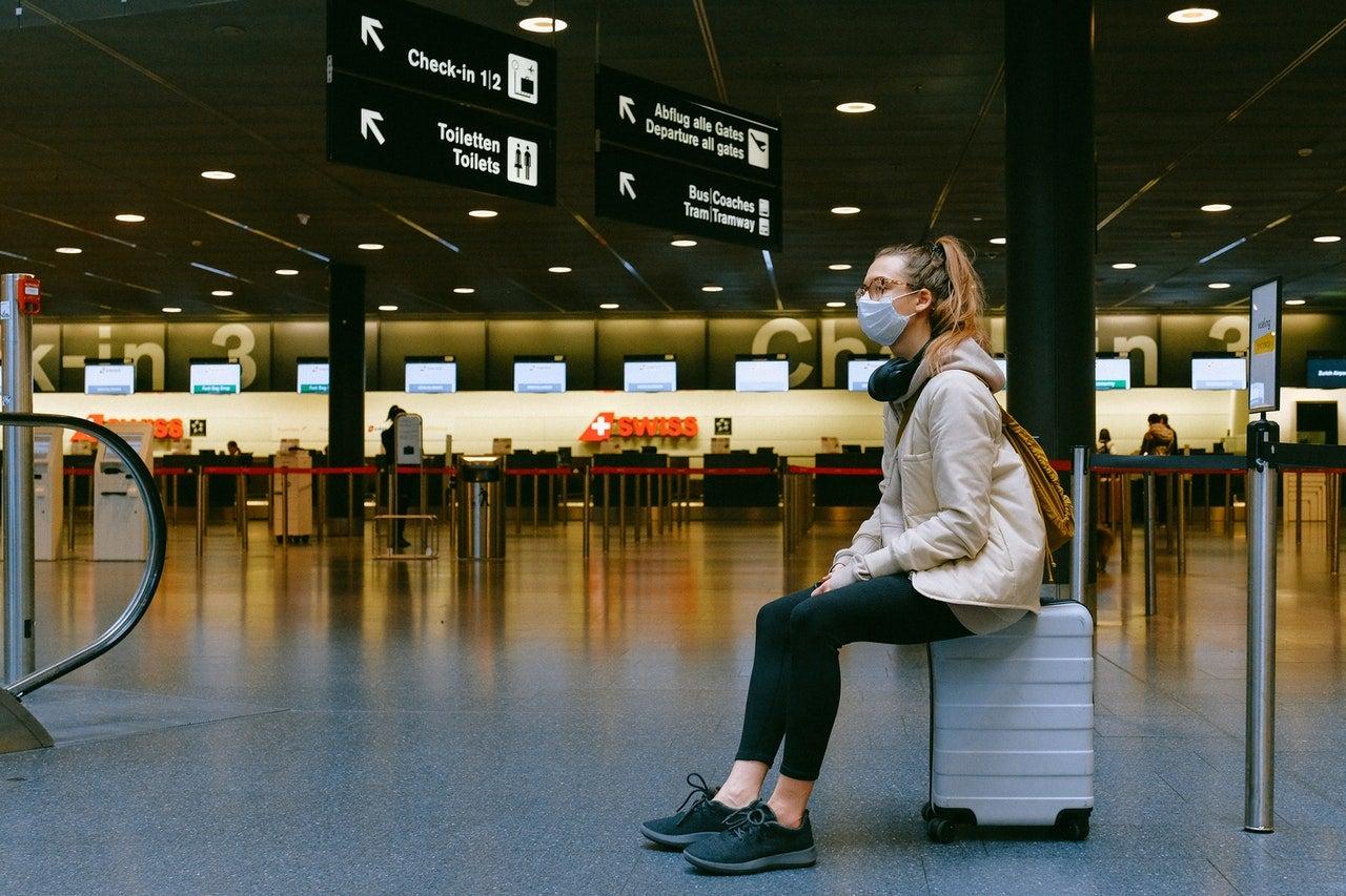 Woman waiting for airplane with coronavirus mask.