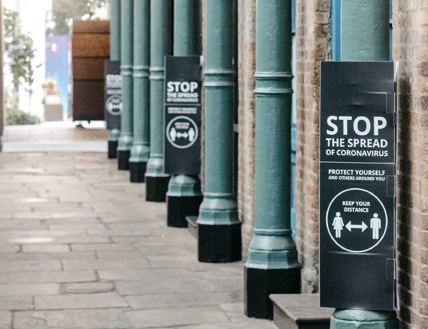 Signs on a city street imploring people to socially distance