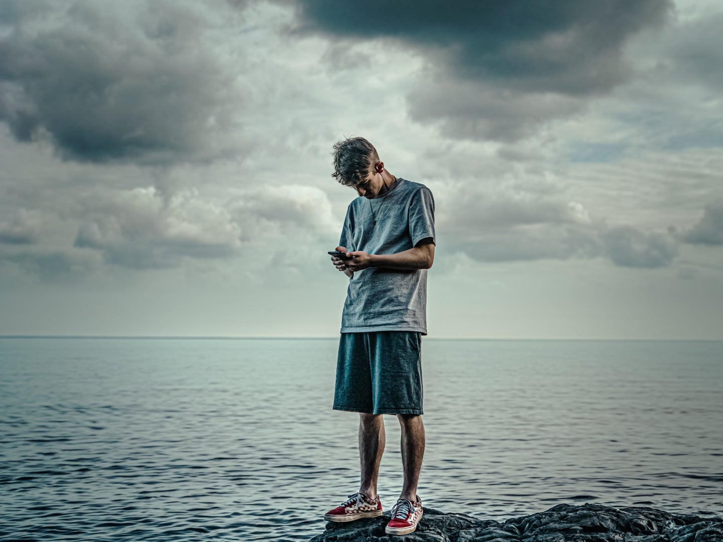 A person standing on a rock by the water under cloudy skies while looking at his phone—hopefully he has a good weather app.