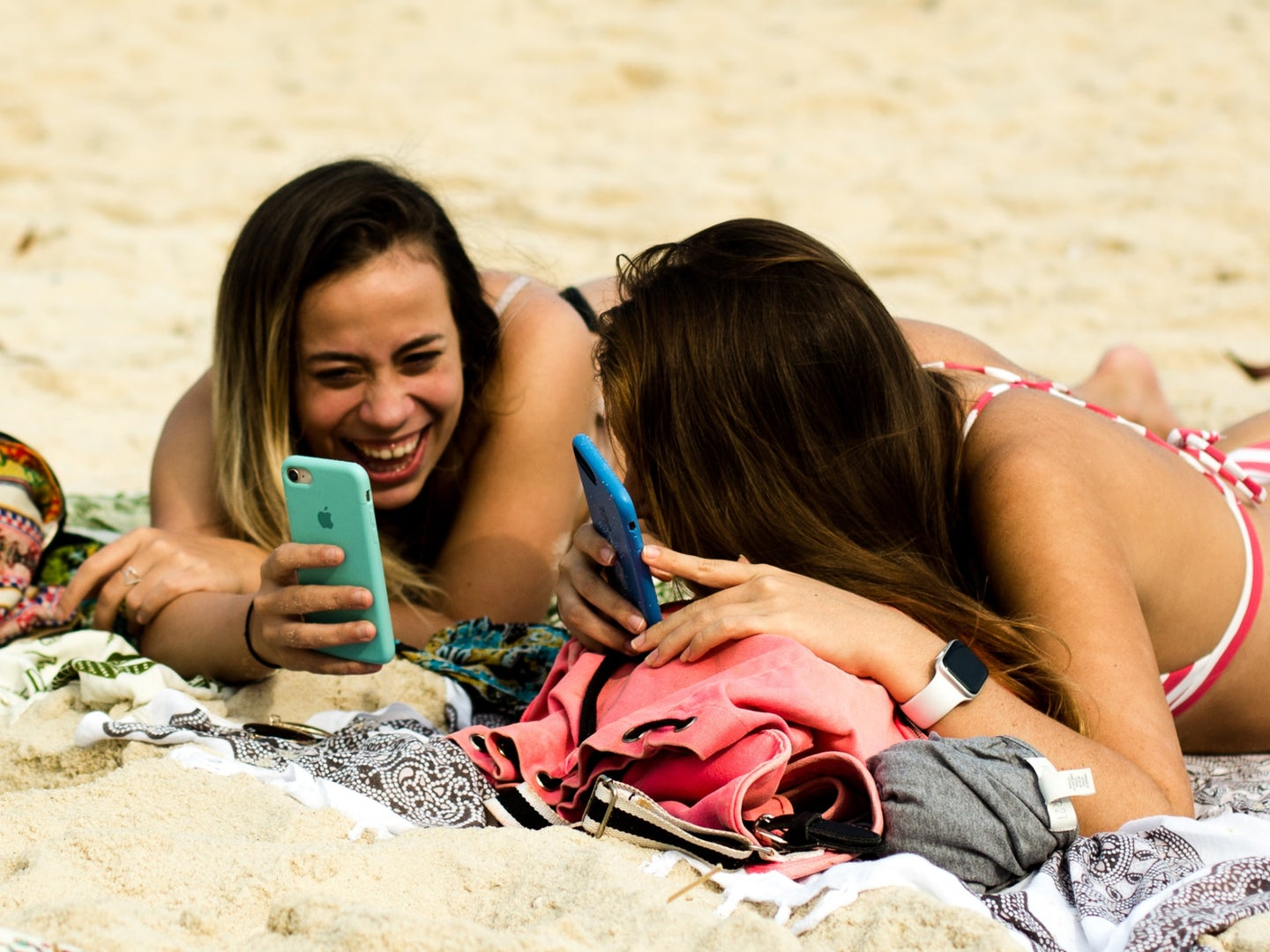 two people on the beach with their phones