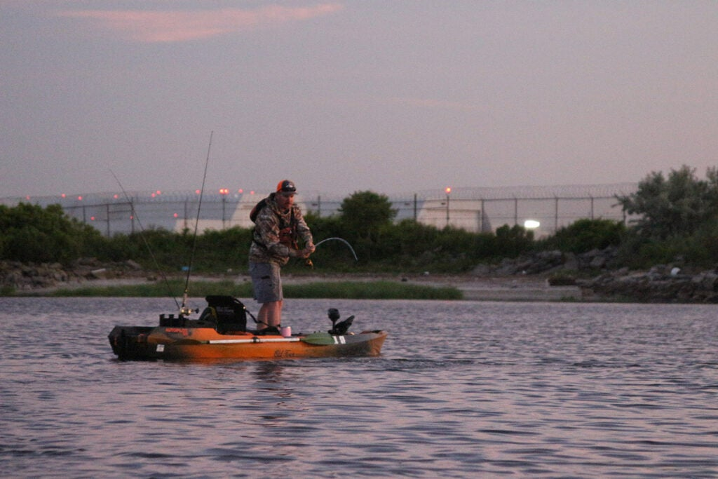 A person fishing off the back of a fishing kayak.
