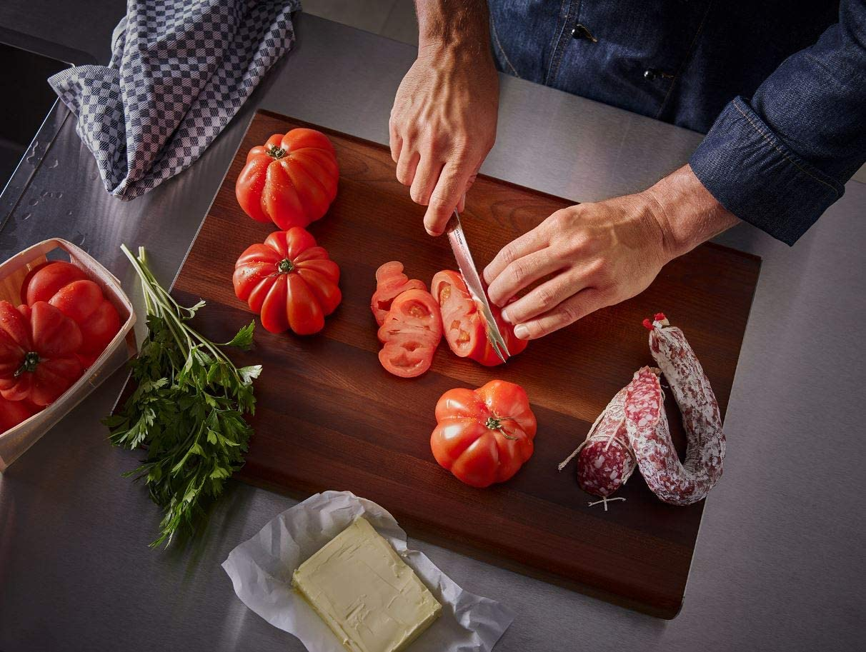 person cutting tomatoes