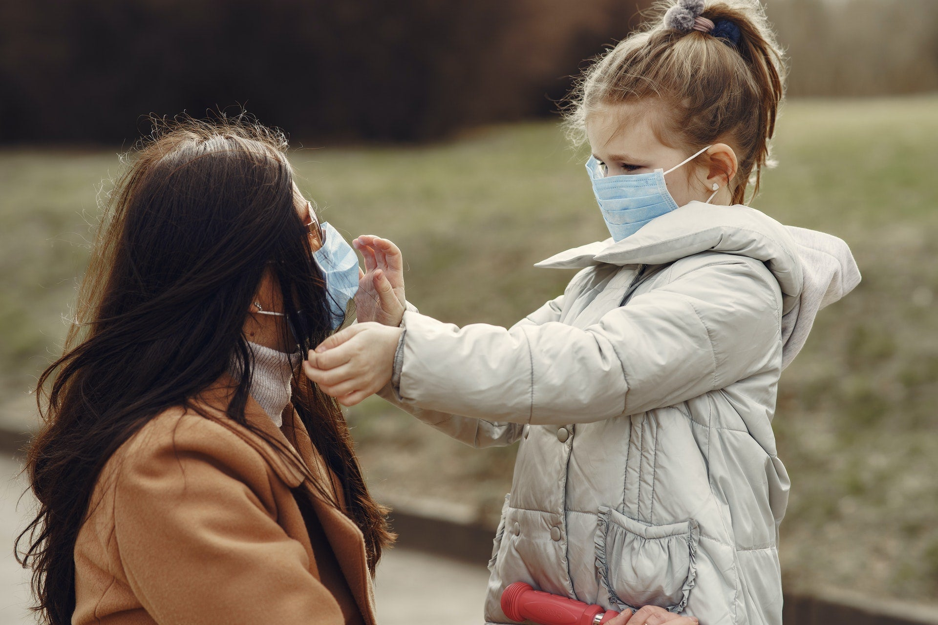 A child in a medical mask touches the face of a woman in a medical mask