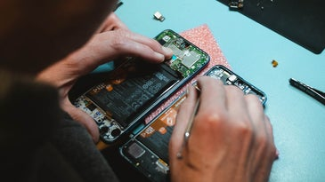 a person working on a disassembled phone