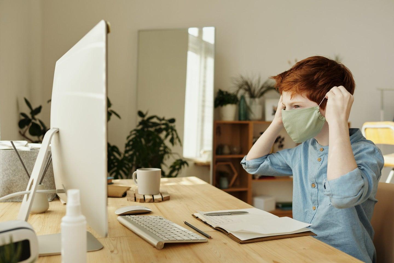Boy doing online school in a mask.
