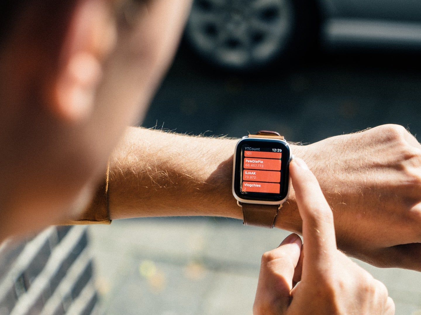 a man using an Apple Watch outside to use his smartphone less