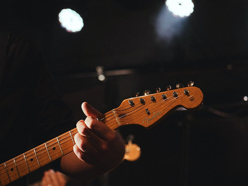 person playing a chord on a guitar