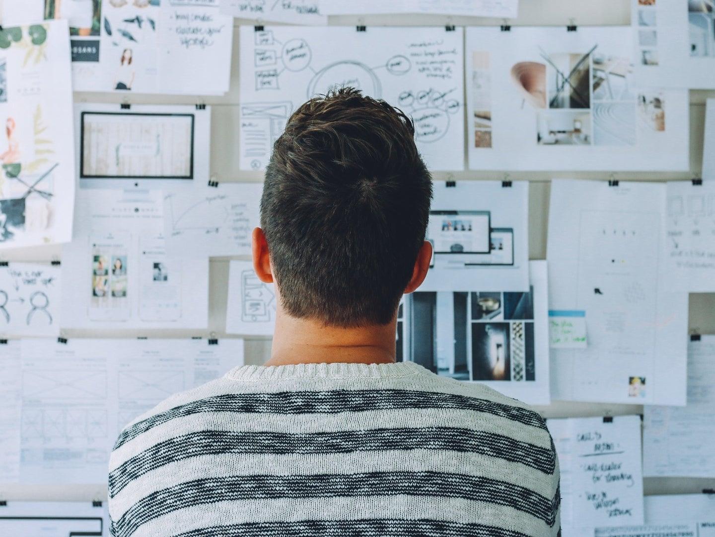 A person contemplates a wall of notes.