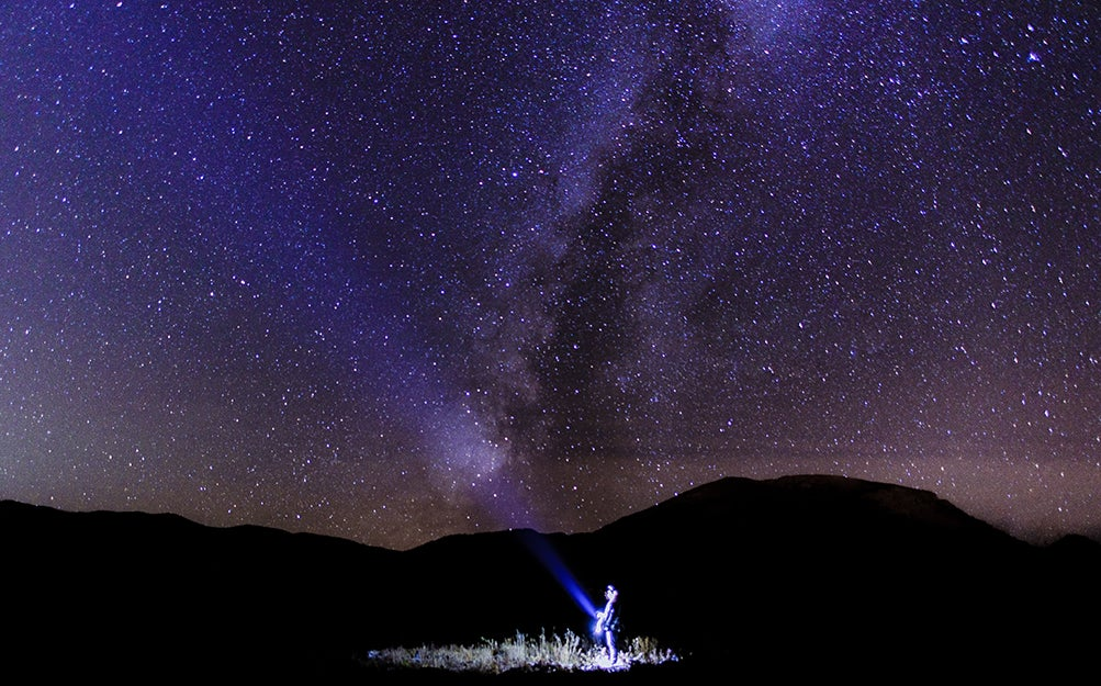 person shining flashlight into the sky