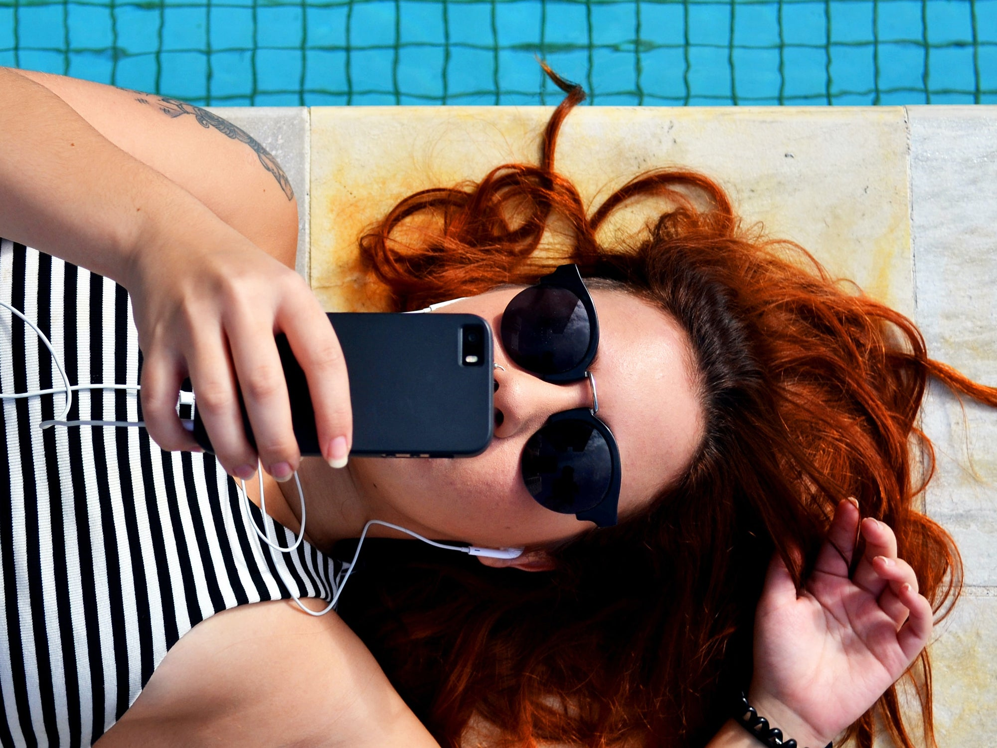 Person looking at phone by the pool