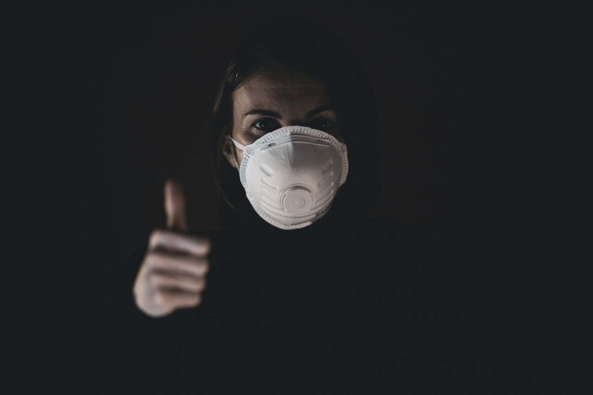 A person wearing an N95 mask and making a thumbs up