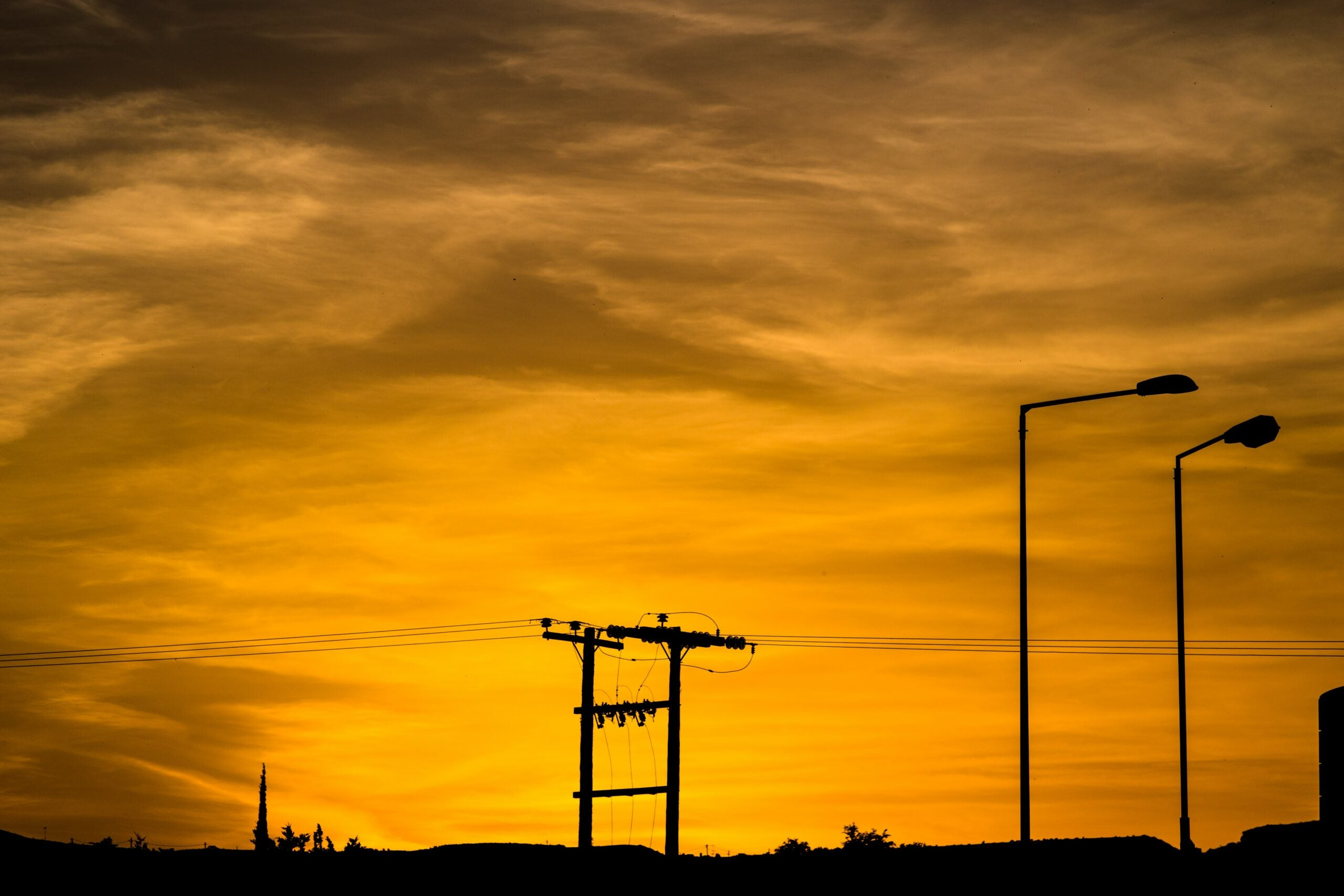 power line silhouette against reddish sunset