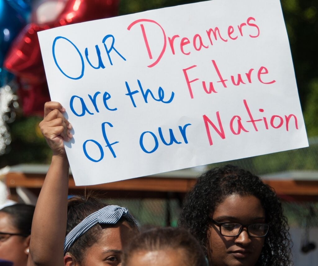 A DACA supporter holds up a sign saying,